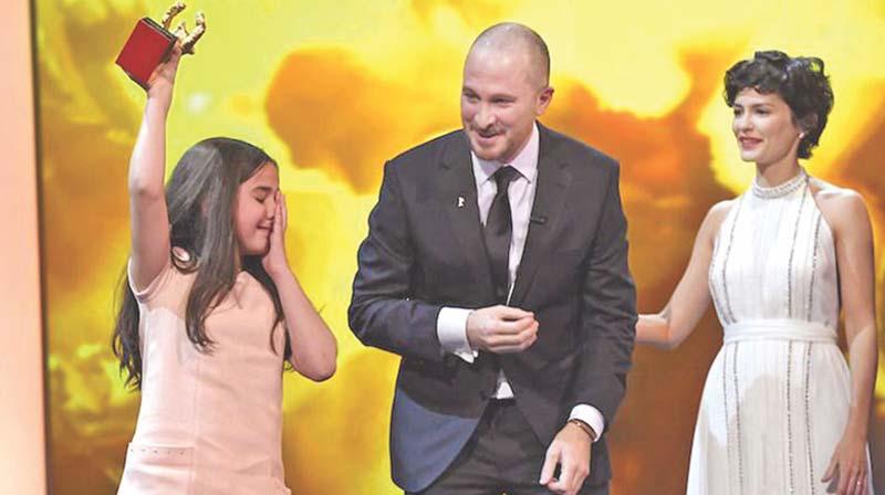 Wzruszona kuzynka (która również występuje w filmie) Panufiego odbiera w jego imieniu Złotego Niedźwiedzia na festiwalu w Belinie.